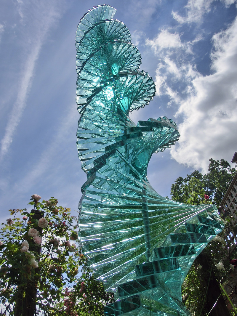 Stacked twisting and turning glass and stainless steel garden sculpture by Tim Carter